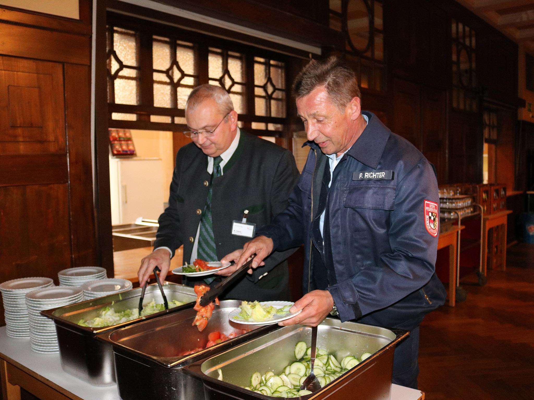 Markus Calana (Kaufmännischer Leiter) und Peter Richter (Leiter der Werkfeuerwehr) testen das vom THW zubereitete Essen. Foto: Bezirkskliniken Mittelfranken