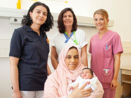 Freuen sich über die Geburt von Lin: Assis- tenzärztin Anna Hakobyan, Stationsleitung Jutta Nauroth, Hebamme Theresa Weiß (v.l.) und Mutter Afas Aldrwish (sitzend). Foto: ANregiomed / Corinna Kern