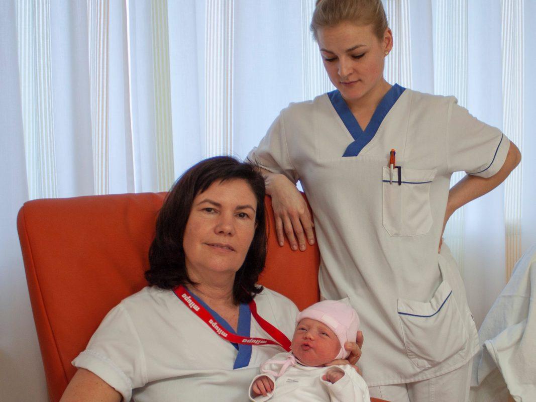 Stationsleitung Jutta Nauroth (sitzend) und Gesundheits- und Krankenpflegeschülerin Amelie Arold freuen sich über Neujahrs- baby Rebecca. Foto: ANregiomed / Corinna Kern