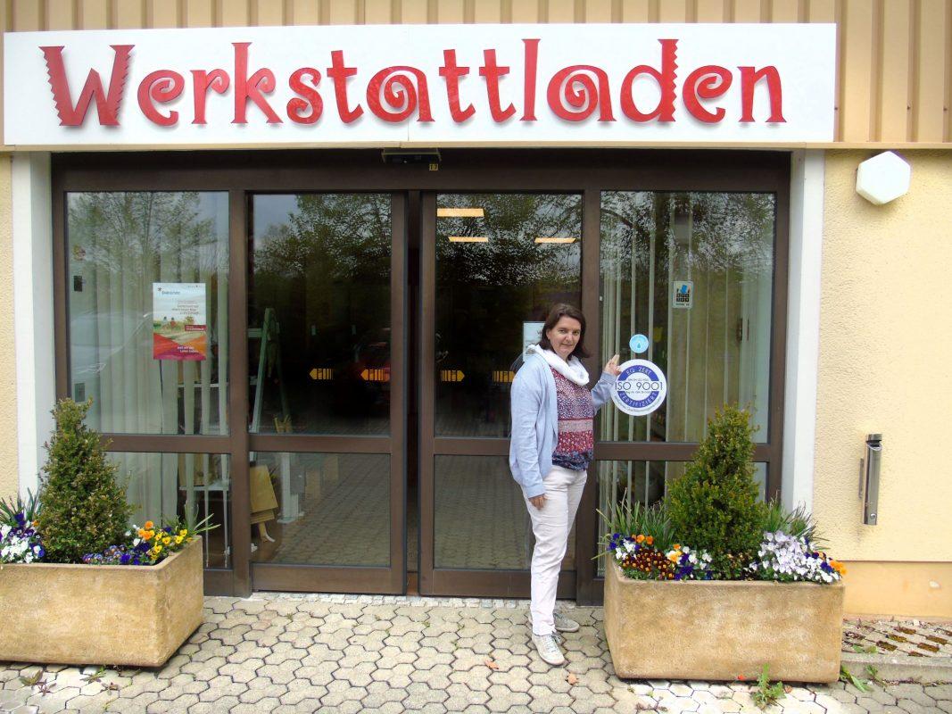 Sandra Lößlein zeigt vor dem Bruckberger Werkstattladen auf den Refill-Aufkleber; Foto: Diakonie Neuendettelsau/Robert Kurth