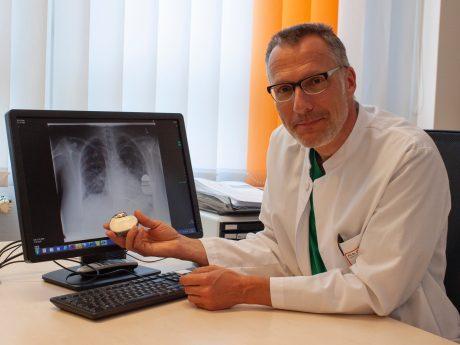PD Dr. Christian Wacker zeigt einen implantierbaren Defibrilla- tor und dessen Lage anhand einer Röntgenaufnahme. Foto: ANregiomed / Corinna Kern