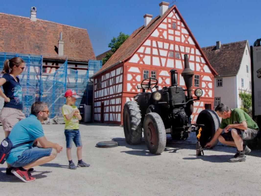 """Freiland-Sommer(-Ferien) """"Hier tut sich was"""". Begeistert führt der Mechaniker des Museums vor, wie man den Lanz-Bulldog anlässt. Foto: Margarete Meggle-Freund."""